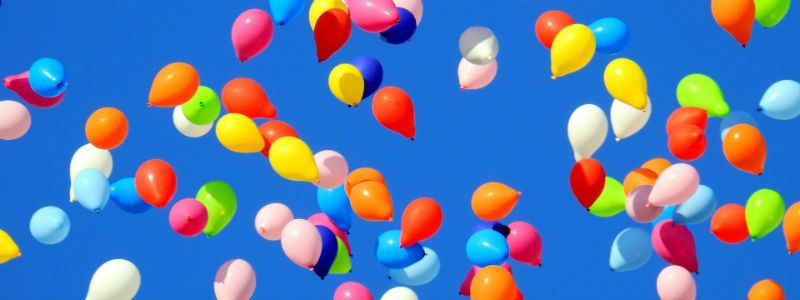 Colourful balloons released into the sky for a celebration of life funeral