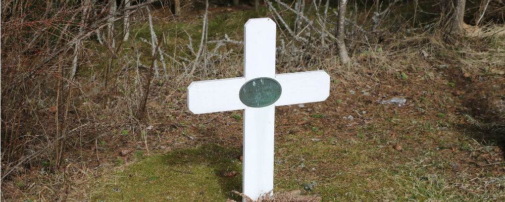 A cross-shaped gravemarker in a cemetery