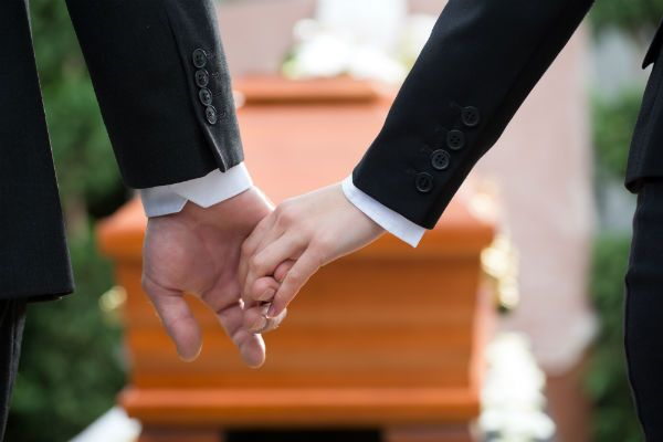 Holding hands in front of a coffin