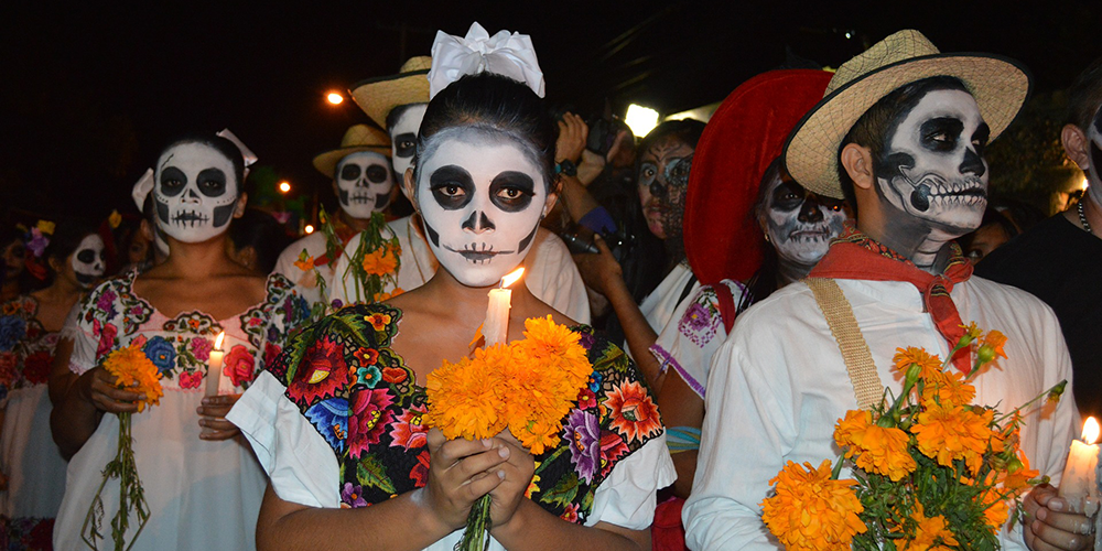 People with traditional sugar skull facepaint carrying marigolds to the cemetery