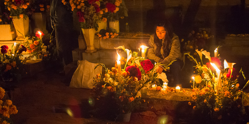 A woman leaving candles and flowers on a loved one's grave on Day of the Dead