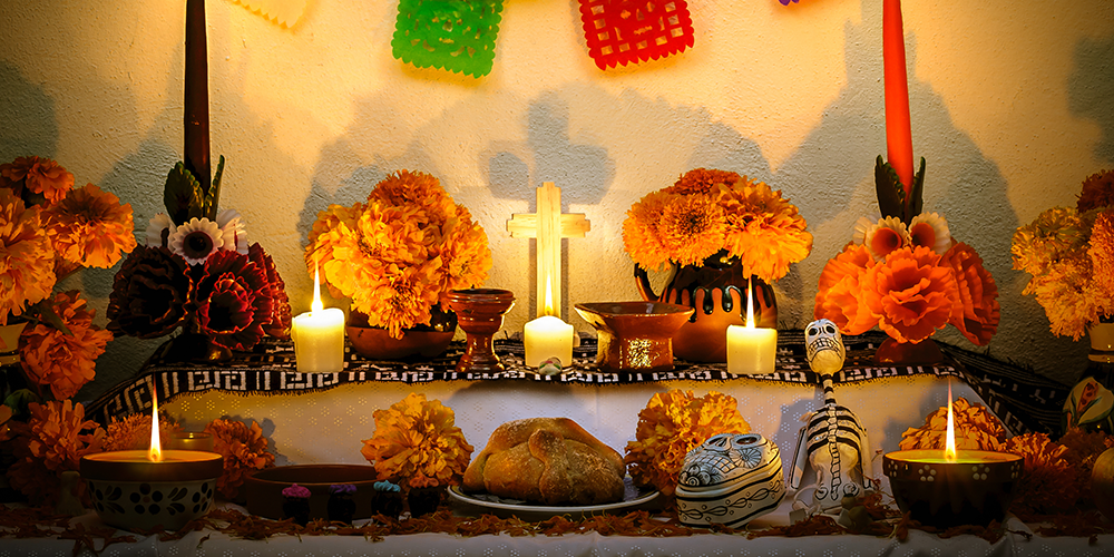 A traditional Mexican Dia de Los Muertos ofrenda, decorated with flowers and candles