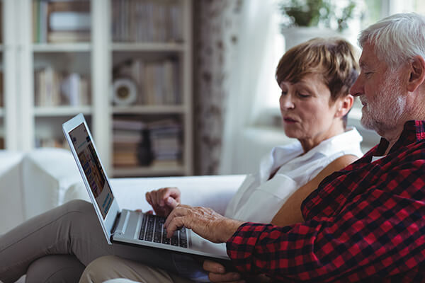 Couple comparing funeral plans online